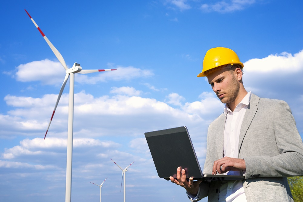 Engineer working on his laptop in front of wind generators