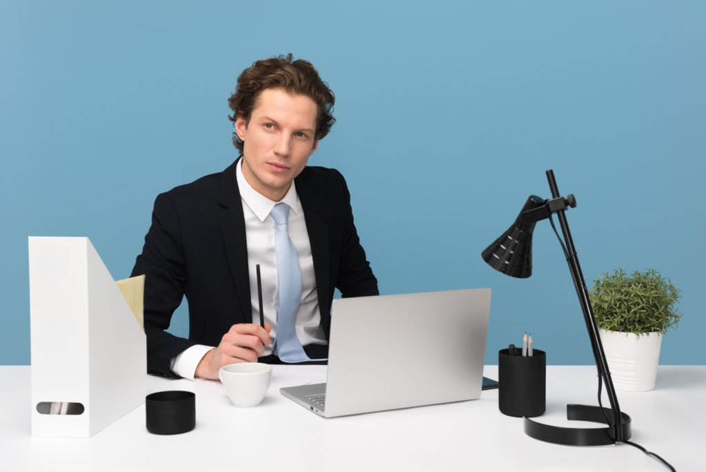 A man in a suit sitting at a desk